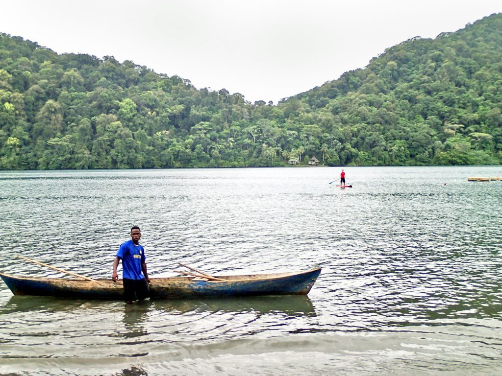 Jascivan Carvalho SUPing the Pacific in Nuqui, Colombia, with a traditional water craft in the foreground